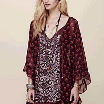 Floral printed chiffon cape-like mini dress with ruffled trimming. Keyhole opening at front of chest with self ties. Oversized, butterfly-style sleeves. Fully lined.