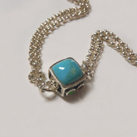 Sterling silver chain bracelet with reversible sterling bead, one side turquoise colored stone, one side filigree scroll