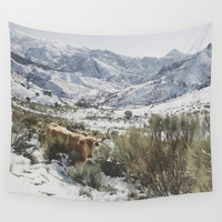 Wild cow at the mountains. Snowing. Wall Tapestry by Guido Montañés