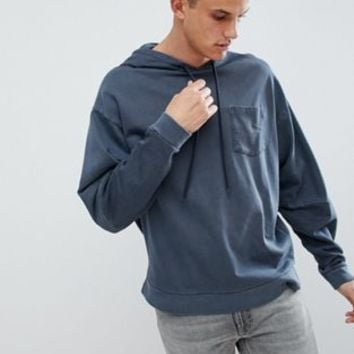 ASOS DESIGN oversized hoodie with cut and sew sleeves in navy vintage wash at asos.com