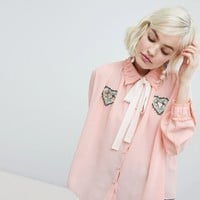 Sister Jane blouse with ribbon tie and heart patch detail at asos.com