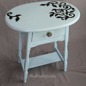 Hand painted whimsical repurposed night stand light blue with black floral decorative motif.