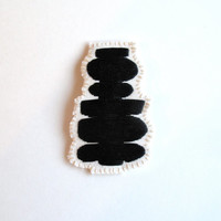 Textile jewelry brooch with black geometric embroidered design on cream muslin and cream felt silver plated pin back