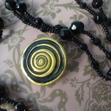 Both a Robyn Gordon BROOCH pin and a BEADED NECKLACE, a swirling black and gold brooch and a long black, beaded necklace, 1990's vintage.