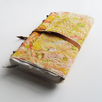 Handmade paper journal with visible and decorative stitch on spine. Hand painted cover orange, green and yellow with 100% cotton paper.