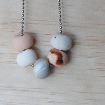 No. 55- Handmade polymer clay beads featuring flesh pink, copper leaf, white/grey marble and white granite beads on a silver chain.