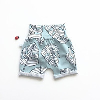 Mint slim fit shorts with white tropical leaves. Comfy toddler or baby shorts. Organic cotton knit fabric.