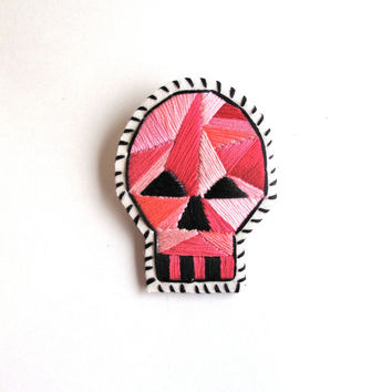 Halloween skull brooch with pink geometric design and black details hand embroidered on cream muslin Halloween Day of the Dead