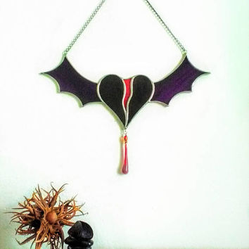Bat wing bleeding heart sin catcher. Blood drop of dark love from a winged heart. Gothic love art glass in deep purple and blood. Love hurts