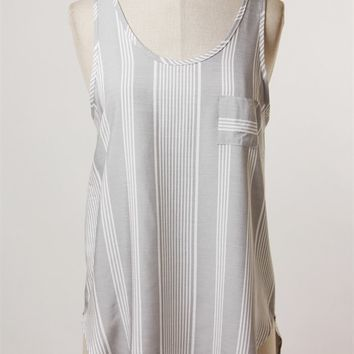 Soft rayon fabrication tank top featuring sleeveless, round neckline, white stripes print throughout, small front pocket construction, and finish asymmetrical hemline. Pair with blue denim cut off and sandals.