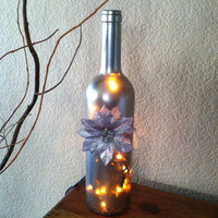 Silver Wine Bottle with white lights. Painted silver and accented with a silver poinsettia.
