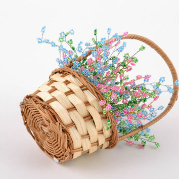 Small basket with handmade bright colorful artificial flowers woven of beads