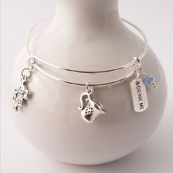 "Alice in Wonderland bangle bracelet featuring tea cup, white rabbit and ""Drink Me"" charms"