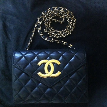 80s Vintage CHANEL black quilted lambskin purse with large CC beak flap tip.