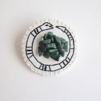 Embroidered snake brooch with cluster of malachite gem beads black and white on cream muslin with felt backing An Astrid Endeavor ouroboros