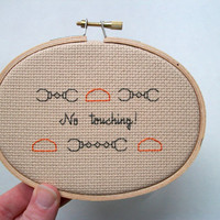AD-inspired No Touching cross stitch -- inspired funny, simple cross stitch, minimalist with orange caps and handcuffs on beige