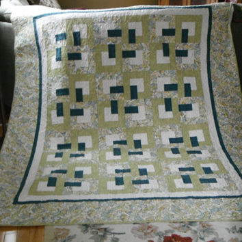 "Twin/Full Size Quilt , featuring a traditional interlocking ""O"" block in  a paisley fabric of soft greens, blues, yellows on white"