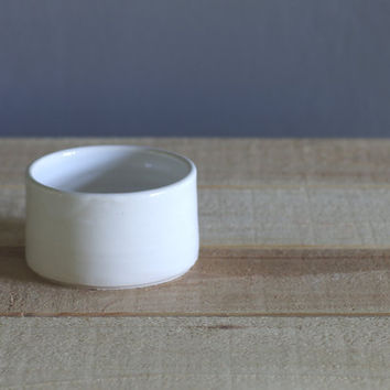 one small open white salt cellar. white gloss glazed porcelain dish. minimal modern pottery ceramic