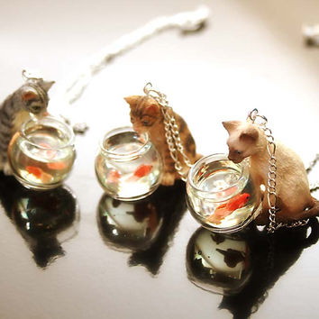 Cat is looking at goldfish in a fish bowl necklace