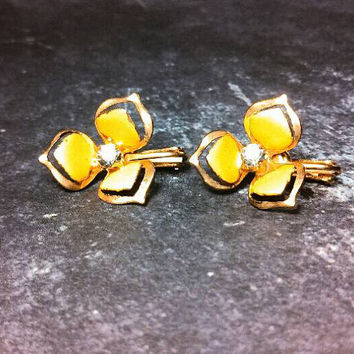 Dainty yellow flower gold tone clip earrings. Painted yellow with a clear rhinestone center. In good vintage condition!