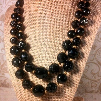 Gold and black bead double strand necklace. Plastic black beads with gold tone beads and gold tone findings.