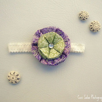 The Lauren headband, purple petals on the outer edge w/ green petals in center and a white button w/ decorative white elastic.