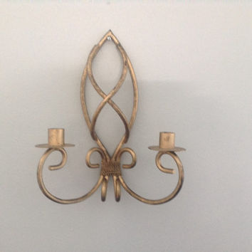 Aged brass painted wrought iron candle sconce.