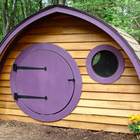 Hobbit Hole Playhouse with round front door and windows, all natural wood construction, purple trim