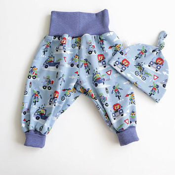 Comfy baby pants and knot hat set. Lions and crocodiles. Blue jersey knit with animals in cars and on bicycles. Baby boy. Knotted hat