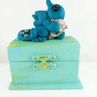 Polymer clay blue baby dragon on an old blue treasure chest