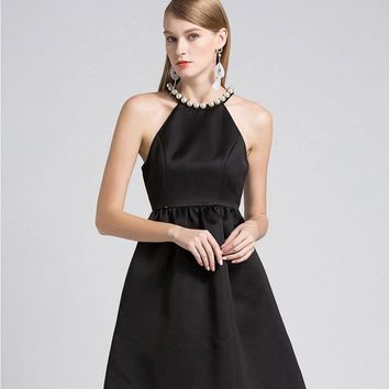 A slim black dress with a black pearl collar and a high waist