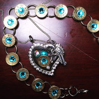 Blue swarovski crystal bracelet and matching heart locket with charms and pistol.