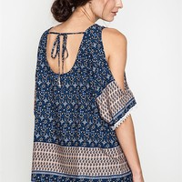 This effortless cold shoulder top features a paisley/flowers print cotton/polyester blended fabric, scoop neckline at front and back with self-tie sash at back, shoulder cutout design, short sleeves with crochet trim, relax fit. Unlined. Pair with denim sh