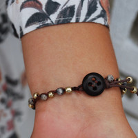 Boho crochet bracelet with blue and gold glass beads and a vintage button clasp with tassel