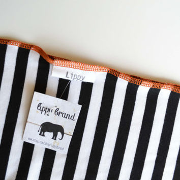 Black and white blanket. Soft and stretchy.  Size 31 by 40 inches. Colors- Black and white with orange edging.   Made by lippy brand.