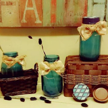 Set of three m a matching mason jars. Beautiful dark transparent blue. Hand painted lids and a touch of burlap for a bow.