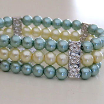 Glass pearl stretch bracelet.  3 strands of glass pearls come together in a multiple strand bracelet. with silvertone bar spacers.