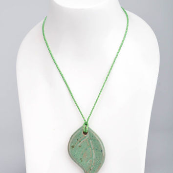 Handmade ceramic small pendant in the shape of light green leaf on a cord