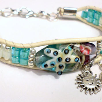 Handmade artisan starfish lampwork glass beaded leather bracelet, beach blue, ivory and silver accent beads, engraved Believe and sun charms
