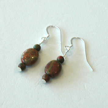 Earrings made from green unakite oval stones on silver wires.