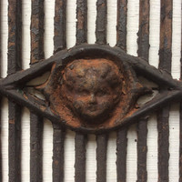 Antique architectural salvage cast iron window guard with cherub face