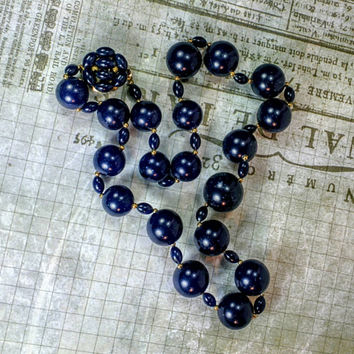 Navy blue bead with white speckled spots, marled. Gold tone findings. Unique clasp! Round ball and oval shaped beads.