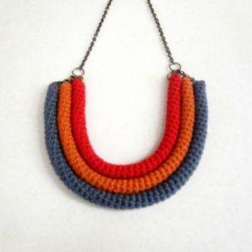 Orbits, crochet bib necklace in red, orange and titanium grey.