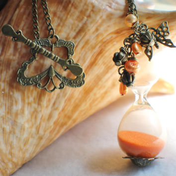 Hourglass sand necklace with charms and bronze accents and orange sand