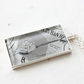 Banjo necklace.  Jewelry made with vintage sheet music illustration of man playing banjo in black and white