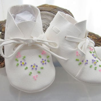 Soft white deer hide moccasins, with delicate beaded floral designs. Sole measures 4 in. heel to toe and 2in. thru ball of foot.