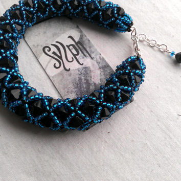Luxurious netted bead-bracelet made out of turquoise and black Czech 11/0 seedbeads and 6mm black bicones