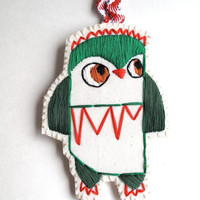 Christmas owl ornament hand embroidered in shades of greens with bright red on cream muslin and cream felt with holiday ribbon loop