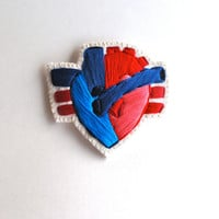 Embroidered anatomical heart brooch with reds and blue on cream muslin with cream felt backing
