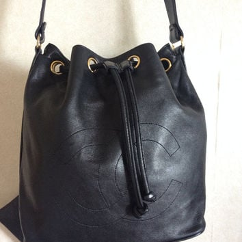 Vintage CHANEL black lamb leather hobo bucket drawstring shoulder bag with drawstrings and CC stitch mark. Classic purse